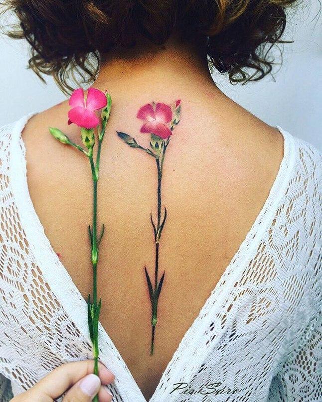 sırta yapılmış minimal renkli çiçek dövmesi