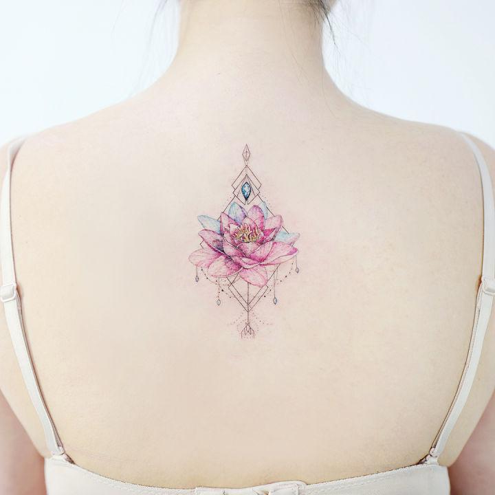 sırta yapılmış minimal suluboya lotus çiçeği dövmesi